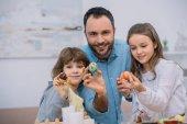 Fotografie Vater und Kinder zeigen Ostern Eiern in die Kamera