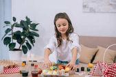 Fotografie happy little child painting easter eggs