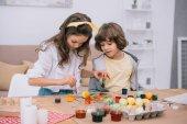 Fotografie konzentrierte kleine Kinder bemalen von Ostereiern