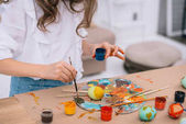 cropped shot of little child painting easter eggs