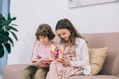 Fotografie Kinder mit Mütter Tag Grußkarten auf couch zu Hause