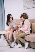 Fotografie děti sedí na pohovce s matkou a ukazuje její blahopřání pro den matek