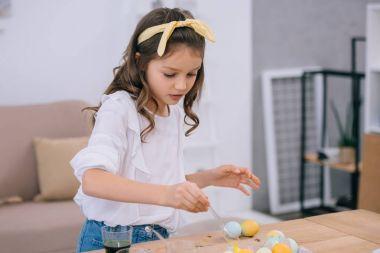 focused little child painting easter eggs