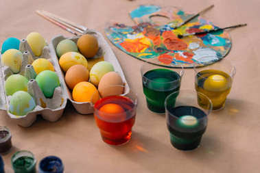 freshly painted easter eggs with paint on table