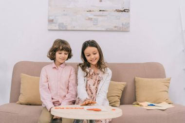 kids preparing greeting for mothers day at home on couch