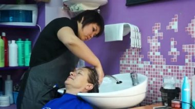 The Barber washes the hair with