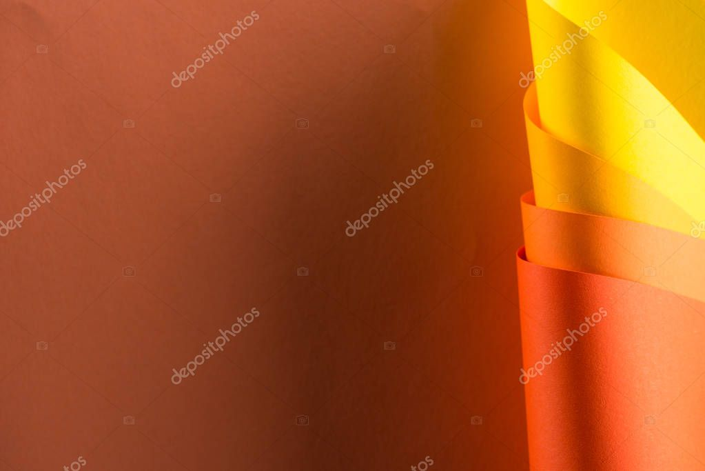rolled colorful papers on brown background