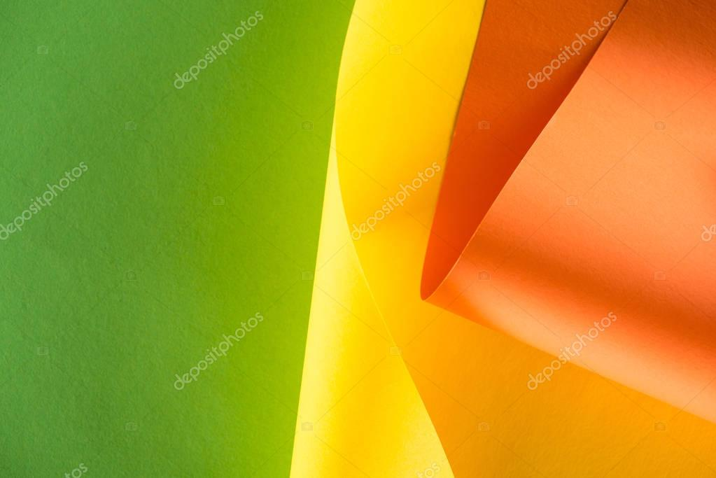 close-up shot of rolled yellow and orange papers on green background