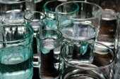 close up view of different sized glasses with water on wooden table