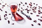 üveg csésze hibiszkusz teát kanállal és asztalon szétszórt tea