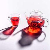 skleněné konvice a šálek s ibišek čaj na desku stolu