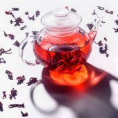 transparent glass teapot with hibiscus tea and scattered tea on table