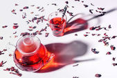 pohled z úhlu vysoké skleněné konvice s ibišek čaj a hrnek s lžičkou na stole