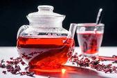 Skleněná konvice s ibišek čaj a hrnek s lžičkou na stole