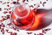 átlátszó üveg teáskanna hibiszkusz és asztalon szétszórt tea