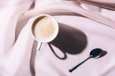 top view of cup of coffee and spoon on pink tablecloth