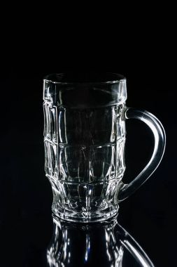 one beer glass on black reflecting surface
