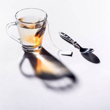 glass cup of black tea and spoon on table