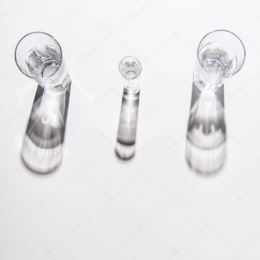 high angle view of different sized glasses with water on white table