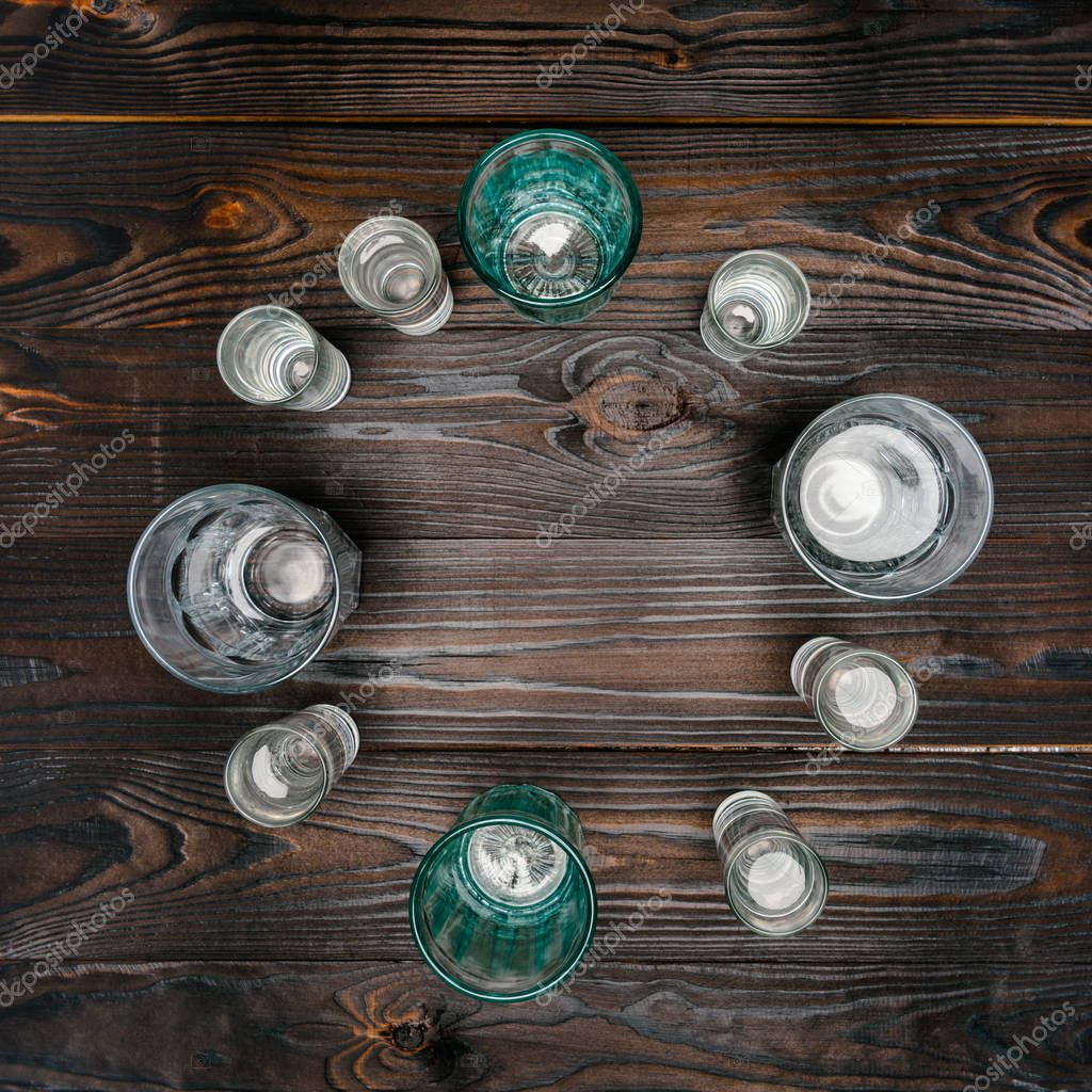 top view of circle with different sized glasses with water on wooden table