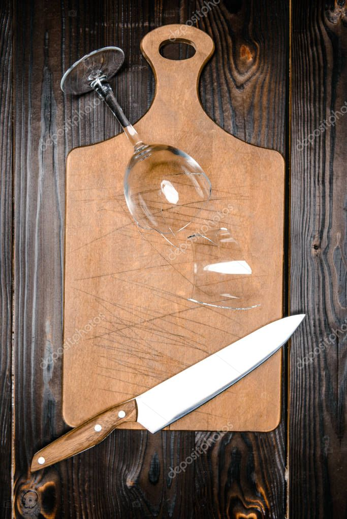 top view of broken wineglass and knife with wooden board on table