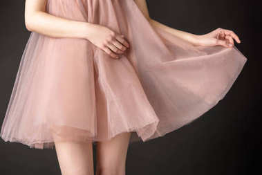 cropped view of tender girl posing in pink chiffon dress, isolated on grey