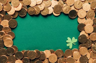 top view of golden coins and shamrock on green table, st patricks day concept