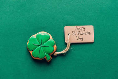 top view of icing cookie in shape of shamrock on green, st patricks day concept