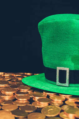 green hat on shining golden coins isolated on black, st patricks day concept