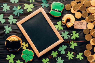 top view of empty board with gingerbread and coins on table, st patricks day concept
