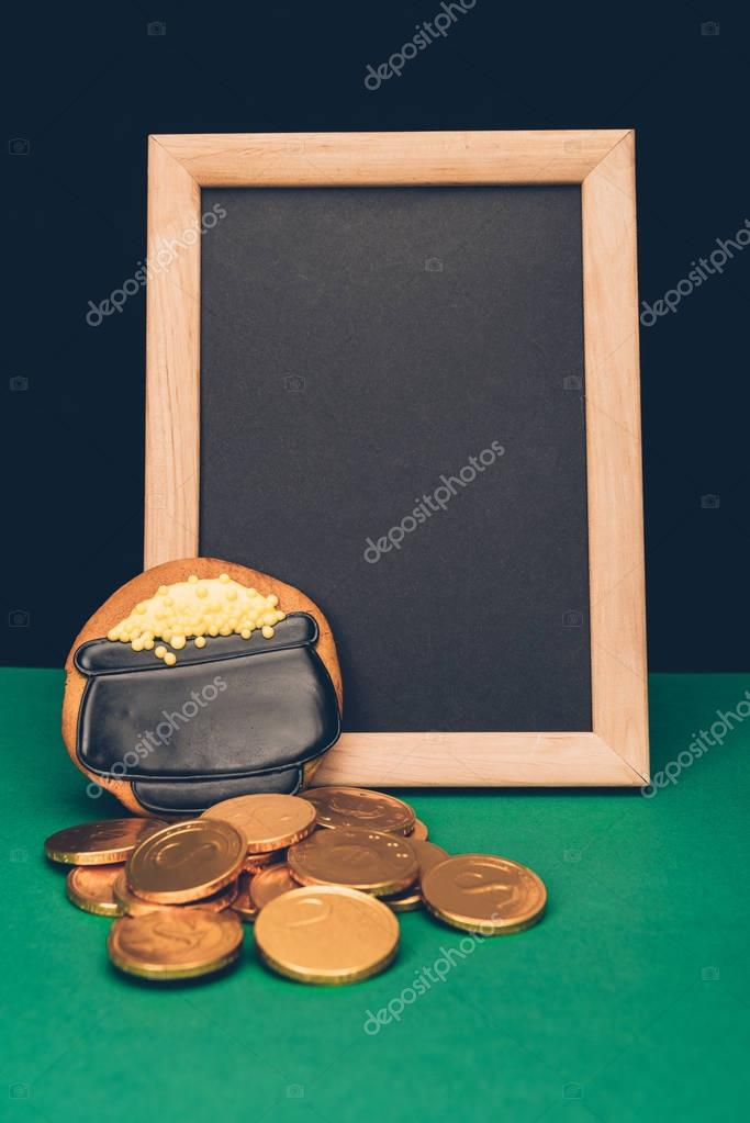 empty board with golden coins and gingerbread on green table, st patricks day concept