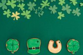 Photo top view of icing cookies and paper shamrock isolated on green, st patricks day concept
