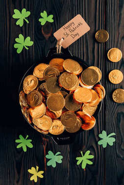top view of pot with golden coins and shamrock on wooden table, st patricks day concept