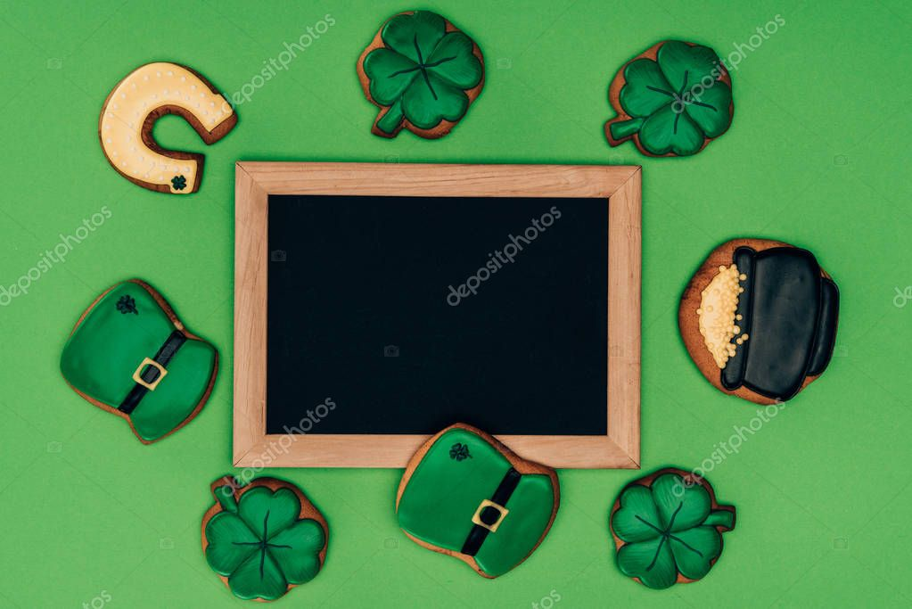 top view of empty board with icing cookies isolated on green, st patricks day concept