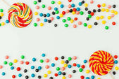 Photo top view of arranged lollipops and candies isolated on white