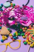 zblízka pohled na Maškarní masky a bonbóny izolovaných na fialová