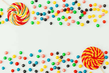 top view of arranged lollipops and candies isolated on white