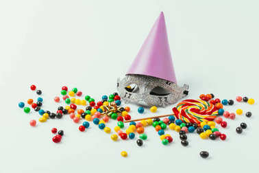 Close up view of masquerade mask, party cone and sweets isolated on grey stock vector