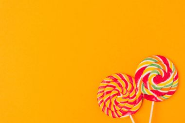 top view of sweet lollipops isolated on orange