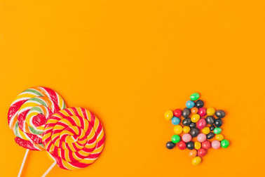 top view of lollipops and star made of candies isolated on orange, purim holiday concept