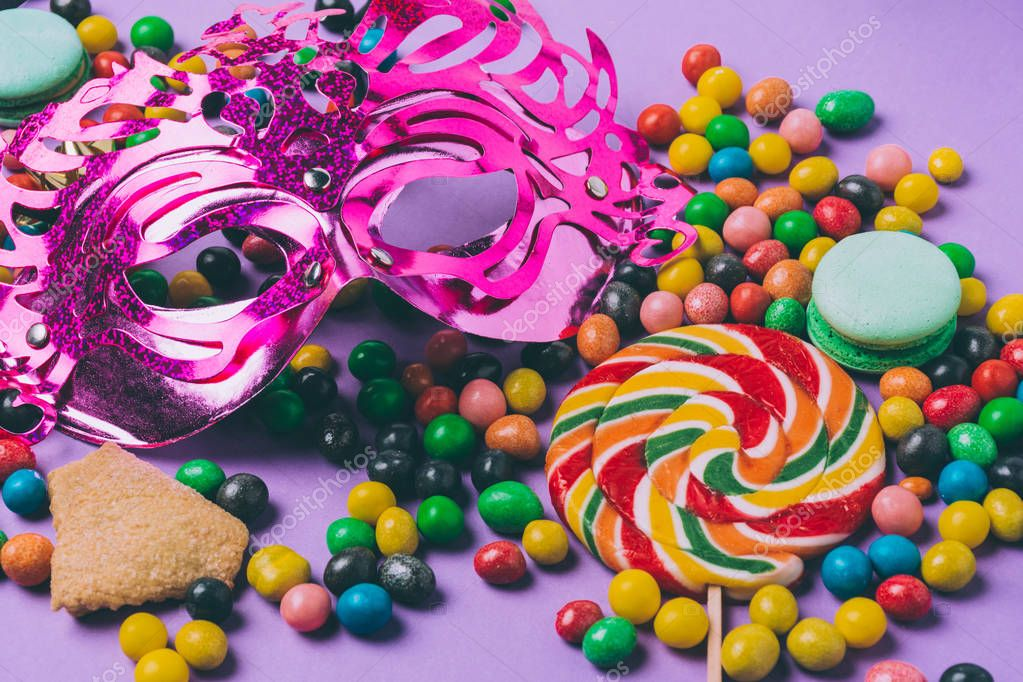 close up view of masquerade mask, lollipop and candies isolated on purple