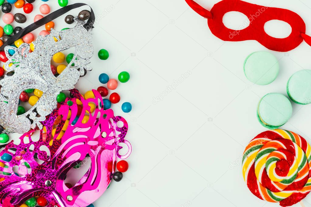 top view of arranged masquerade masks, macarons and candies isolated on grey, purim holiday concept