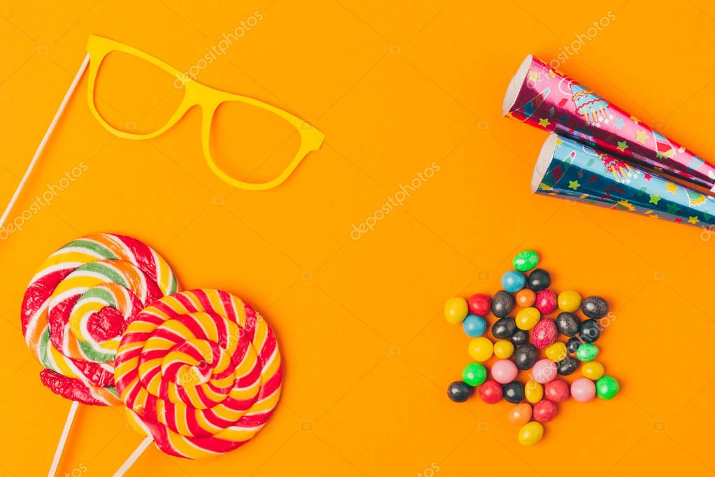 flat lay with sweets, lollipops and party objects isolated on orange, purim holiday concept