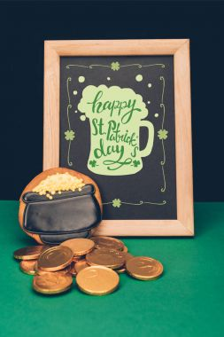 close up view of festive cookie, golden coins and blackboard with happy st patricks day lettering, st patricks day holiday concept