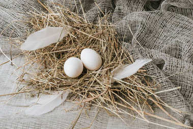 white eggs laying on straw over sackcloth