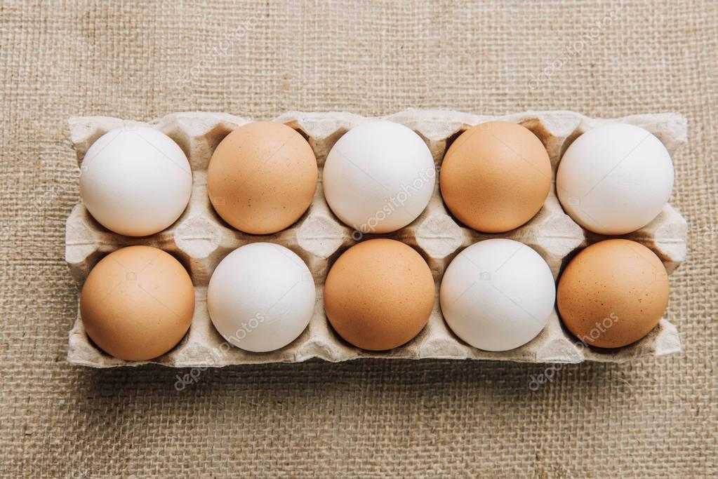 white and brown eggs laying in egg carton on sackcloth