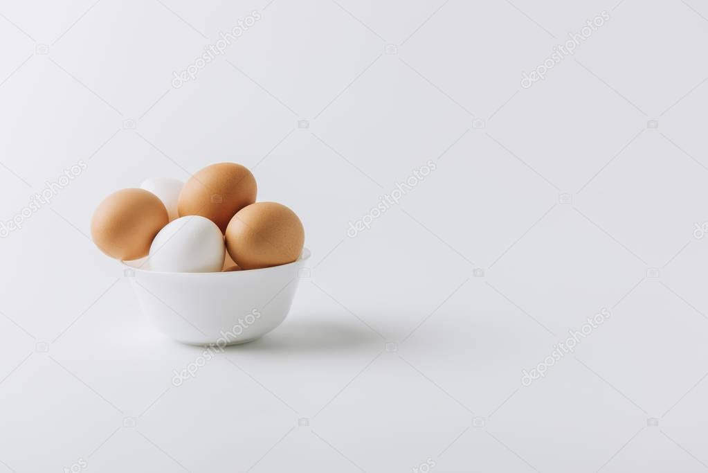 white and brown eggs laying on white plate on white background