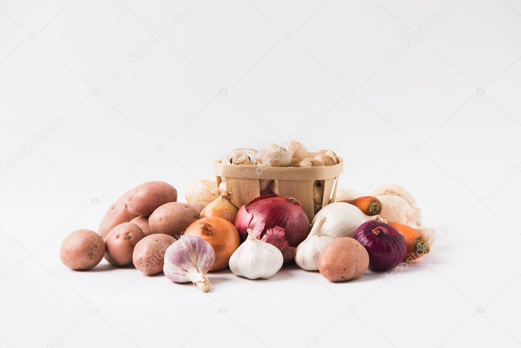 heap of mushrooms laying in basket over vegetables on white background