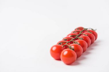 raw cherry tomatoes laying on white background