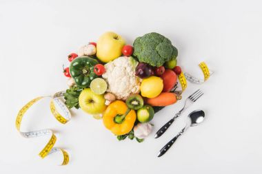vegetables and fruits laying on white background with fork, spoon and measuring tape